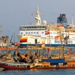 The M/V Africa Mercy in port in Cotonou, Benin with fishing canoes in the foreground